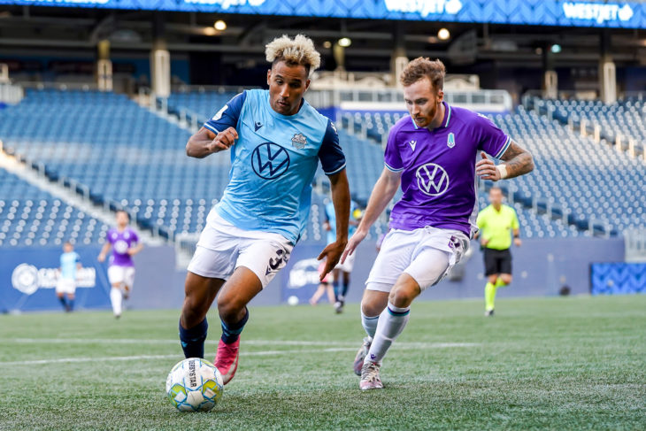 July 13, 2021. HFX Wanderers FC vs Pacific FC. Second-Half. Morey Doner of HFX Wanderers FC plays the ball away from Josh Heard of Pacific FC.